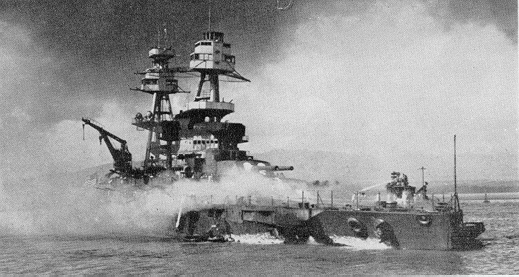 El USS Nevada varados después de su intento de salir del puerto. El remolcador de la Armada Hoga se afana en extinguir el fuego sobre la proa del USS Nevada